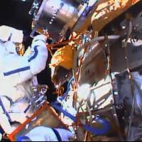 This photo taken from video provided by NASA shows Russian cosmonauts Yuri Malenchenko and Sergey Volkov install fresh experiments outside the International Space Station on Wednesday. | NASA VIA AP