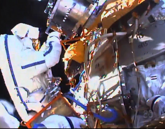 ISS cosmonauts step out, toss commemorative flash drive, snag test samples