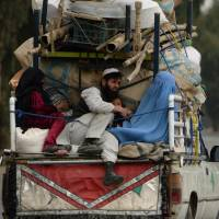 In this photograph taken on Wednesday an internally displaced Afghan family rides on the back of a vehicle with their belongings as they flee from military operations against militants in Kot district in Nangarhar province. | AFP-JIJI