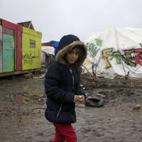 Aida, a 9-year-old Kurdish girl, walks in the mud in the southern part of a camp for migrants called the 'Jungle' during a rainy winter day in Calais, northern France, Monday. French authorities have asked migrants living in tents and makeshift shelters in the southern sector to leave the area. | REUTERS