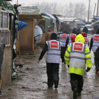 Volunteers from 'Care 4 Calais' walk between makeshift shelters in the southern part of a camp for migrants called the 'Jungle' Monday. | REUTERS