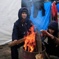 Two migrants from Kuwait try to warm up in a camp for migrants called the 'Jungle', in Calais, northern France, Thursday. A French judge on Thursday upheld a government plan to partially demolish a shanty town for migrants trying to reach Britain on the outskirts of Calais. | REUTERS