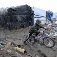 A young boy from Afghanistan pushes his bycicle in the mud in the southern part of the camp known as the 'Jungle' in Calais, northern France, Thursday. | REUTERS