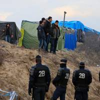 Migrants stand near tents as French riot policemen look on in the camp known as the 'Jungle' Thursday. | REUTERS