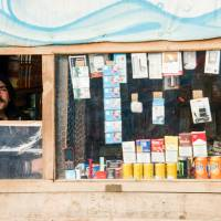 A Pakistani migrant selling cigarettes stands in his shop on Thursday in the 'Jungle' migrants and refugee camp in Calais, northern France. | AFP-JIJI