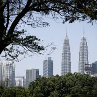 Malaysia's landmark building, Petronas Twin Towers and other buildings are framed under a tree in Kuala Lumpur Sunday. Australia has warned that terrorists may be plotting attacks in and around Kuala Lumpur, Malaysia's largest city, according to a travel advisory from The Australian High Commission in Malaysia. | AP