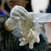 A Bureau of Customs appraiser shows to the media a set of jewelry from the Roumeliotes Collection, one of three sets of the Marcos Jewelry Collection, during appraisal at the Central Bank of the Philippines in Manila last November. | AP