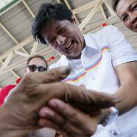 Vice-presidential candidate Sen. Ferdinand 'Bongbong' Marcos Jr. autographs the palm of a supporter during his campaign sortie in Muntinlupa city, southeast of Manila, on Feb. 22.  Three decades after a People Power revolt ousted his dictator father, Sen. Ferdinand Marcos Jr. is wooing voters on the campaign trail this week in his bid to become the Philippines' next vice president. | AP