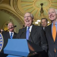 Senate Majority Leader Mitch McConnell, flanked by fellow Republicans, laughs while meeting with reporters on Capitol Hill in Washington Tuesday following a closed-door policy meeting. | AP