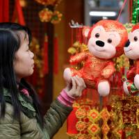 A woman looks at a decorative monkey at a shop selling red lanterns and Lunar New Year decorations in the old quarter of Hanoi on Saturday. | AP
