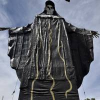 A devotee passes a figure of Santa Muerte, or 'Death Saint,' during a celebration at an outdoor temple in Tultitlan, Mexico, on Sunday. | AFP-JIJI