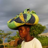 Malawian subsistence farmer Louise Abele carries corn she bought to feed her family near Lilongwe on Jan. 31. | REUTERS