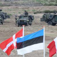Flags wave in front of soldiers taking position during the NATO Noble Jump exercise on a training range near Swietoszow Zagan, Poland, on June 18, 2015. Poland on Feb. 3 welcomed a U.S. plan to quadruple military spending in Europe in reaction to Russia's military resurgence. | AP