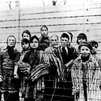 Children standing behind barbed wire in Auschwitz are photographed just after the camp's liberation by the Soviet Army in Poland in January 1945. | AP