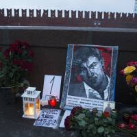 Flowers, votive candles and portraits of slain Russian opposition leader Boris Nemtsov stand at the spot where he was gunned down on Feb. 27 last year, with the Kremlin Wall in the background, in Moscow early Saturday. The sign in the center reads, '1 year.' | AP