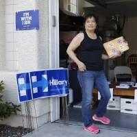 Chinese-American Cynthia Ameli (center) picks up materials from Sarah Gibson before heading out to canvass for presidential candidate Hillary Clinton in Las Vegas on Friday. Asian-American voters are the fastest-growing racial group in the U.S. and both parties increasingly are wooing them. | AP