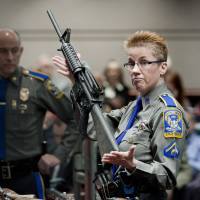 Firearms training unit Detective Barbara J. Mattson, of the Connecticut State Police, holds up a Bushmaster AR-15 rifle, the same make and model of gun used by Adam Lanza in the Sandy Hook School shooting, during a hearing of a legislative subcommittee, at the Legislative Office Building in Hartford, Connecticut, in January 2013. | AP