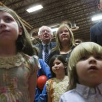 Democratic presidential candidate Sen. Bernie Sanders (center) watches the for results with his wife, Jane during a primary night party at Concord High School on Tuesday in Concord, New Hampshire.   AP