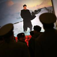 Soldiers are silhouetted against a portrait of North Korean leader Kim Jong Un in Pyongyang at a festival as part of celebrations Monday, a day ahead of the birthday anniversary of late North Korean leader Kim Jong Il. | AP