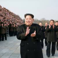 North Korean leader Kim Jong Un attends a photo session with scientists, technicians and others who worked on the country's Earth-observation satellite launched on Feb. 7 in this undated picture. | REUTERS