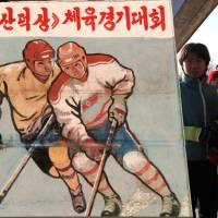 North Korean children pass a signboard depicting ice hockey players in this undated photo taken in Pyongyang. | MICHAEL SPAVOR