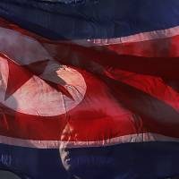 A North Korean man carries his country's national flag at the Pyongyang Indoor Stadium in the nation's capital on Feb. 16. | AP