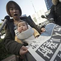 A woman takes an extra edition of a newspaper reporting North Korea's rocket launch in Tokyo on Sunday. North Korea defied international warnings and launched a long-range rocket Sunday that the United Nations and others call a cover for a banned test of technology for a missile that could strike the U.S. mainland. | AP
