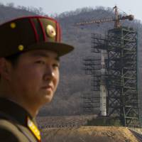 A North Korean soldier stands in front of the Unha-3 rocket at the launch site in Tongchang-ri in April 2012. | AP