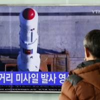 A man watches a television news program in Seoul on Thursday reporting about North Korea's recent rocket launch.   AP