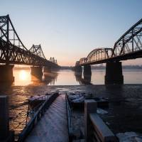 The sun rises over the bridge on the banks of the Yalu River in the Chinese border town of Dandong opposite to the North Korean town of Sinuiju on Tuesday. | AFP-JIJI