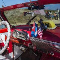 The stars and stripes and the Cuban national flag are placed together on the dashboard of a vintage American convertible in Havana Thursday. President Barack Obama said that he will visit Cuba on March 21-22, making him the first sitting president in more than half a century to visit the island nation.   AP