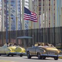 Tourists ride vintage American convertibles as they pass by the United States Embassy in Havana Thursday.   AP
