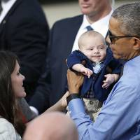 President Barack Obama holds 3-month-old Charlie Allsup as he meets with the crowd before departing on Air Force One at Moffett Federal Airfield Thursday in Mountain View, California. | AP
