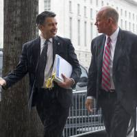 Nevada Gov. Brian Sandoval (left) and Wyoming Gov. Matthew Mead talk as they walk in the rain upon arriving at the National Governors Association Winter Meeting in Washington, Sunday. | AP