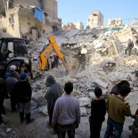 Civil defense members search for survivors after airstrikes by pro-Syrian government forces in the rebel held al-Qaterji neighborhood of Aleppo, Syria, Sunday. | REUTERS