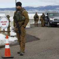 FBI agents man an entry as Harney County residents protest the FBI's presence at the Burns Municipal Airport in Burns, Oregon, Sunday. | REUTERS