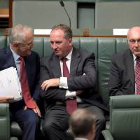 Australian Prime Minister Malcolm Turnbull (left) speaks to Australian Agriculture Minister Barnaby Joyce (center) as Federal Minister for Infrastructure and Regional Development Warren Truss sits next to them in the House of Representatives at Parliament House in Canberra on Thursday. Joyce was elected leader of the Nationals party the same day, automatically making him deputy prime minister. | REUTERS
