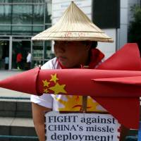 A protestor from the League of Filipino Students and Kabataan (Youth) Party list group holds an effigy symbolizing a missile and placards during a rally by more than a dozen students outside the Chinese Consulate in Manila's Makati financial district Friday. | REUTERS