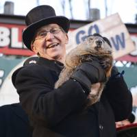 Groundhog co-handler Ron Ploucha holds up Punxsutawney Phil after on Gobbler's Knob on the 130th Groundhog Day in Punxsutawney, Pennsylvania, on Tuesday. Punxsutawney Phil emerged from his burrow on Tuesday and predicted an early spring. | REUTERS