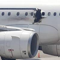 A hole is seen Tuesday in a plane operated by Daallo Airlines at the airport in Mogadishu. | AP