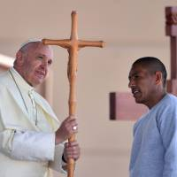 Pope Francis receives a cross made by an inmate during his visit to the CeReSo n. 3 penitentiary in Ciudad Juarez, Mexico, Wednesday. | AFP-JIJI