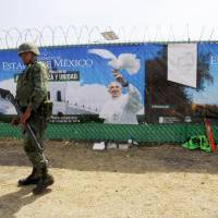 A soldier stands guard during the open-air Mass celebrated in Ecatepec —a rough, crime-plagued Mexico City suburb — on Sunday. Pope Francis has chosen to visit some of Mexico's most troubled regions during his five-day trip to the world's second most populous Catholic country. | AFP-JIJI