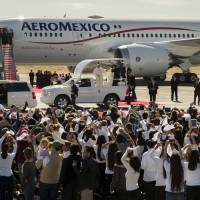 People wave and take pictures of Pope Francis in his popemobile as he arrives to Benito Juarez International Airport in Ciudad Juarez, Mexico, Wednesday. | AP
