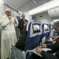 Pope Francis gestures during a meeting with the media onboard the papal plane while en route to Rome Wednesday. | REUTERS