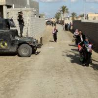 Civilians flee to a safe area with help from Iraqi security forces in Jweba on the eastern fringes of Ramadi on Monday. Iraqi forces recaptured territory from Islamic State militants on Tuesday that links the recently recaptured city of Ramadi to a major army base in western Iraq, the military said. | REUTERS