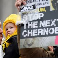 A demonstrator holds a child next to an anti-nuclear activist holding up a placard reading 'Stop the next Chernobyl' during a protest over the lack of safety of Belgian nuclear power plants, outside the Belgian Interior Ministry in Brussels on Monday during a meeting of Germany's environment minister with Belgium's interior minister. | AFP-JIJI