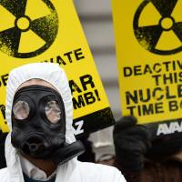 An anti-nuclear activist wearing a gas mask takes part in a protest over safety concerns at Belgian nuclear power plants, outside the Belgian Interior Ministry in Brussels on Monday. | AFP-JIJI