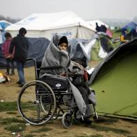A temporarily stranded Syrian refugee is seen on a wheelchair in a field at a makeshift camp next to the Greek-Macedonian border, near the Greek village of Idomeni, Wednesday. | REUTERS