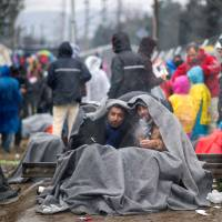 A photo taken from behind a fence at the Macedonian side of the border shows men sitting under a blanket and smoking cigarettes as they wait with other migrants from Syria to cross the Greek-Macedonian border near the town of Gevgelija on Wednesday. Balkan countries along the well-trodden migrant path toward Northern Europe met Wednesday to explore ways to stem the flow despite growing fears that tighter controls will spark a humanitarian crisis, particularly in Greece. | AFP-JIJI