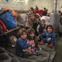 Children rest in a camp with other migrants and refugees waiting for a train to Serbia near Gevgelija, at the Macedonian-Greek border, on Wednesday. | AFP-JIJI